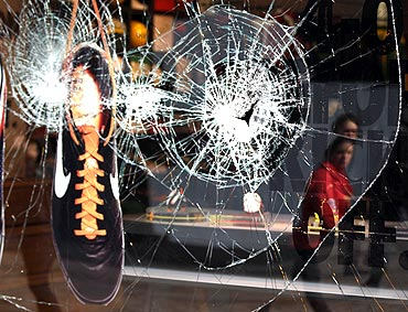A shoe hangs in the smashed window of the Nike store in Manchester, northern England