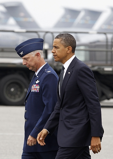 Obama walks with USAF Col Mark Camerer, 436th Airlift Wing Commander, after he arrives at Dover Air Force Base in Delaware