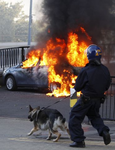 A policeman and his dog walk towards a burning car in central Birmingham, central England
