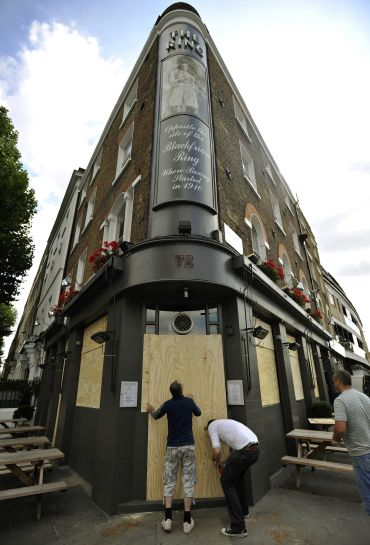 A publican boards up his pub in central London