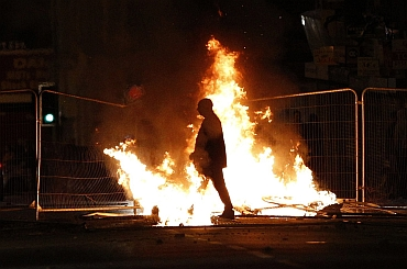 A rioter walks through a burning barricade in Liverpool