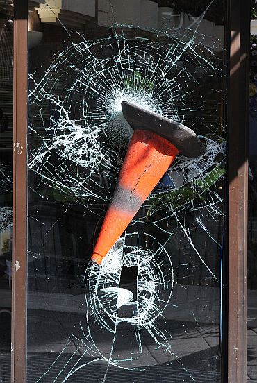 A traffic cone is embedded in the smashed windows of a shop