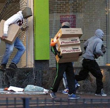 Looters carry boxes of electronic products