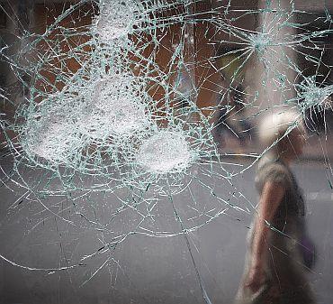 A woman walks past a broken cafe window