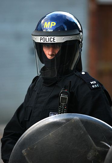 A riot police officer stands guard