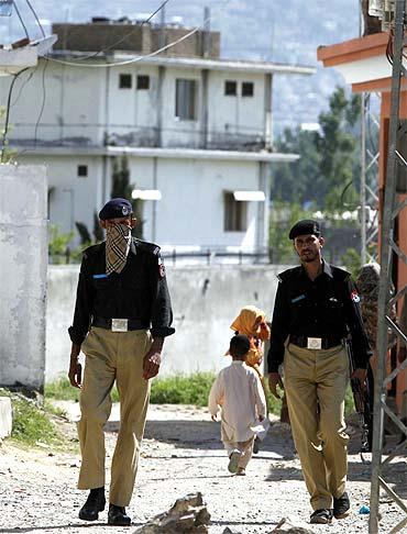 Pakistani policemen patrol a street near the compound where Al Qaeda leader Osama bin Laden was killed by US troops in Abbottabad