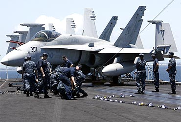 US Navy personnel work in front of a F/A-18 Hornet fighter jet on the flight deck of the aircraft carrier USS Carl Vinson anchored off the Manila bay, where Osama bin Laden was given burial ritual