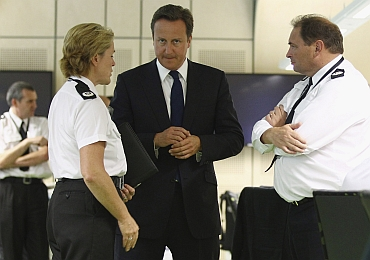 British PM David Cameron is shown the West Midlands Police events control suite by Chief Constable Chris Sims (R) and Assistant Chief Constable Sharon Rowe, in Birmingham central England