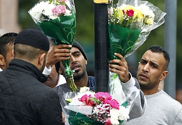 Locals place floral tributes at the scene where three men were killed by a car in the Winson Green area of Birmingham