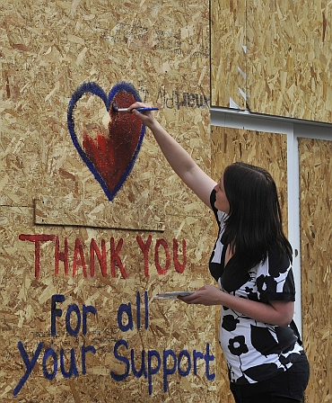 A woman paints a message on a boarded up shop in Ealing