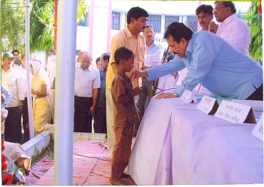 State government official hands over a beneficiary cheque to a child from the Mahadalit community