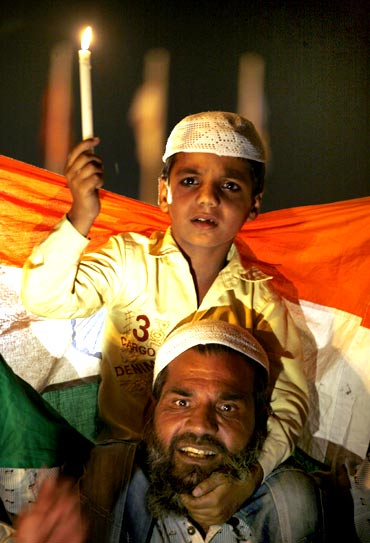 A supporter of social activist Anna Hazare and his child attend a candlelight campaign against corruption at India Gate in New Delhi