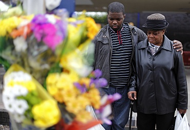 A man comforts a woman as she looks at floral tributes for three men killed by a car during the recent rioting in the Winson Green area of Birmingham