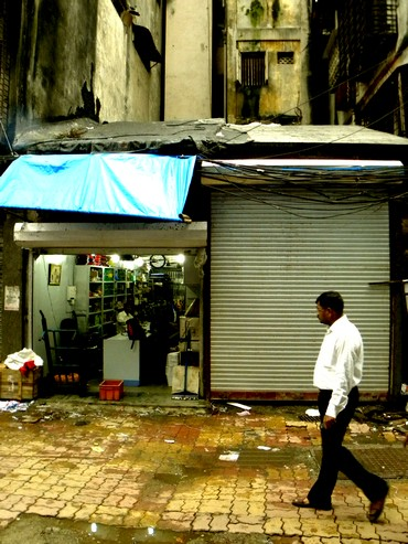 A passer-by walks past ground zero in Zaveri Bazaar. The shop with the shutter down was where the blast took place