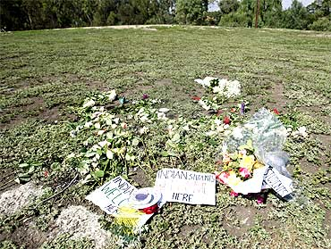 Flowers and candles are placed at a park in memory of Nitin Garg, who was stabbed and killed in Melbourne