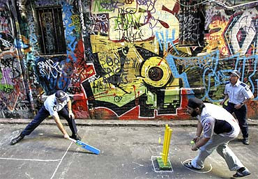 Indian students and policemen play a game of laneway cricket in Melbourne to promote harmony