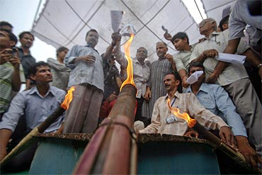 Supporters of activist Anna Hazare burn copies of the Lokpal Bill