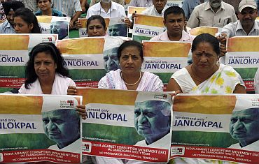 Supporters of Anna Hazare hold his portraits during a rally against corruption