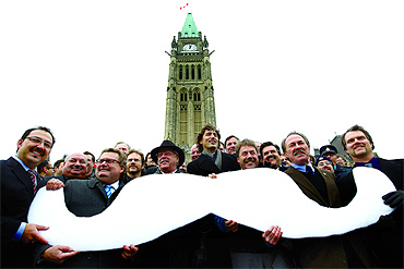 Members of Parliament and staff who grew moustaches in November last year hold a cut-out of a moustache during an event to mark the end of 'Movember' on Parliament Hill in Ottawa November 30, 2010. The group raised more than $30,000 for prostate cancer research.