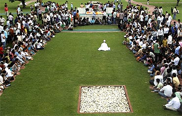 Anna Hazare, surrounded by his supporters, prays at Rajghat