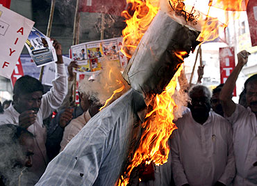 Activists burn an effigy representing the United Progressive Alliance government during a rally in support of Hazare