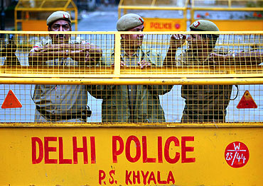 Policemen stand guard behind a barricade at the site of Hazare's proposed fast