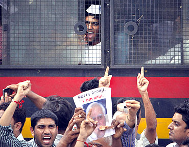A supporter of Hazare shouts anti-government slogans from a police vehicle after being detained during a protest rally