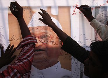 Supporters of Anna Hazare sign a banner with a portrait of Hazare outside the Tihar jail in New Delhi