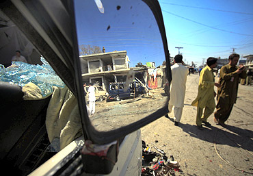 The site of a suicide bomb blast is reflected in the side mirror of a damaged vehicle in Charsadda, northwest Pakistan