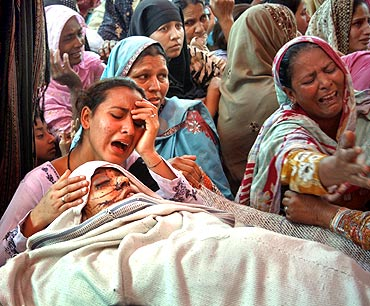A woman mourns her mother who was killed during suicide bomb attacks in Dera Ghazi Khan