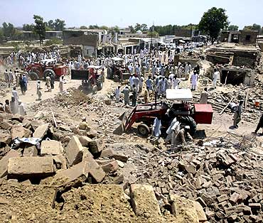 Tractors move rubble from the site of a suicide bomb blast in Pakistan's Pashtun tribal region