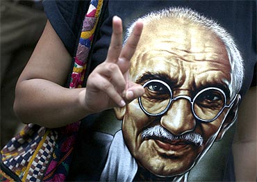 A supporter of Hazare flashes a victory sign while wearing a T-shirt with a photo of Mahatma Gandhi