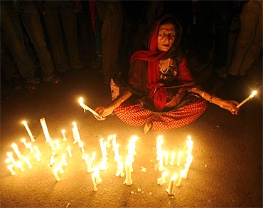 A supporter of Anna Hazare prays during a candlelight protest against corruption in New Delhi