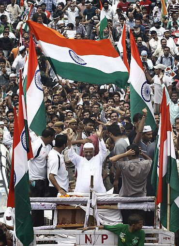 Anna Hazare (C, wearing white cap) waves from a vehicle after he left Tihar jail in New Delhi