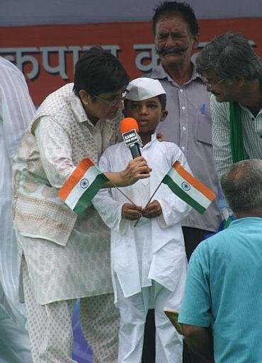 Kiran Bedi with a school kid on stage