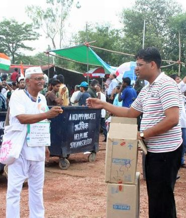 An India Against Corruption volunteer distributes biscuits to protestors at Ramlila Maidan