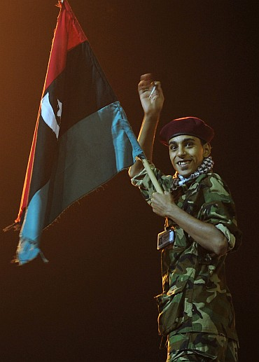 A Libyan gestures while holding a Kingdom of Libya flag as people gather near the courthouse in Benghazi
