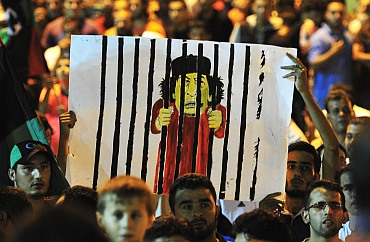 Men hold a cartoon of Gaddafi in Benghazi to celebrate the entry of rebel fighters into Tripoli. Jubilant rebel fighters streamed into the heart of Tripoli as Gaddafi's forces collapsed and crowds took to the streets to celebrate, tearing down posters of the Libyan leader