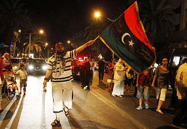 A member of the Libyan community in Tunisia holds the Kingdom of Libya flag as others gather outside the Libyan Embassy in Tunis