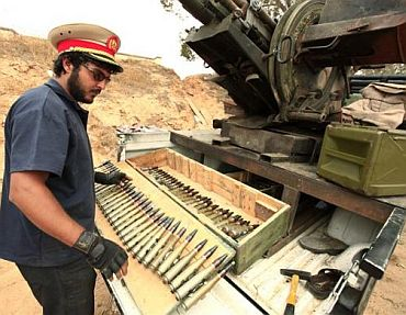A Libyan rebel fighter prepares anti-aircraft ammunition as he wears the cap of a pro-Muammar Gaddafi officer at Misrata's western front line, some 25 km (16 miles) from the city centre, June 4
