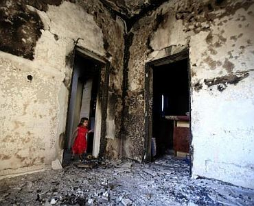 A girl stands in the doorway of a home destroyed in battles between rebel fighters and forces loyal to Muammar Gaddafi on Tripoli street in central Misrata May 29