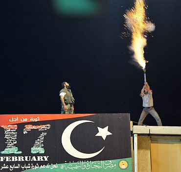 A man lets off fireworks near the courthouse in Benghazi August 22 to celebrate the entry of rebel fighters into Tripoli