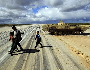 A man walks with his children past an army armoured vehicle at a military airport runway in the eastern Libyan town of Al Abrak February 24