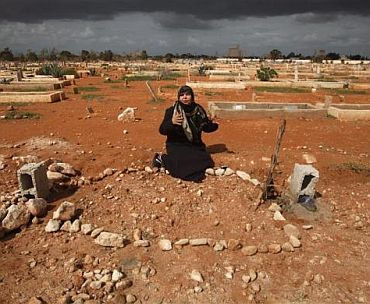 The mother of Salem Al-Moqlah, a Libyan who was killed in the clashes, reacts next to his grave in a cemetery in Benghazi February 26