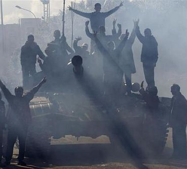 A Libyan army tank manned by soldiers opposed to leader Muammar Gaddafi is surrounded by protesters in the city of Zawiyah, 50 km (30 miles) west of the capital Tripoli March 1
