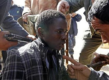 Rebels hold a young man at gunpoint, who they accuse of being a loyalist to Libyan leader Muammar Gaddafi, between the towns of Brega and Ras Lanuf, March 3