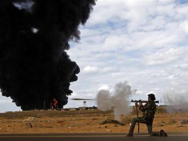 A rebel fighter fires a rocket-propelled grenade launcher in front of a gas storage terminal during a battle on the road between Ras Lanuf and Bin Jiwad, March 9