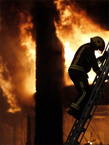 A firefighter climbs a ladder in Tottenham in riot-struck London on August 7