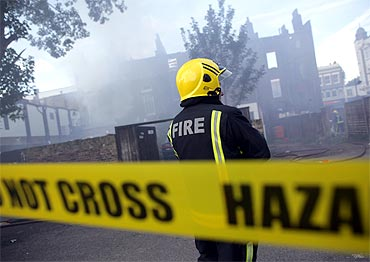 A fireman stands outside a burning building after riots on Tottenham High Road in London