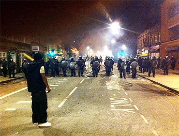 Protestors face off against riot police lines on Tottenham High Road